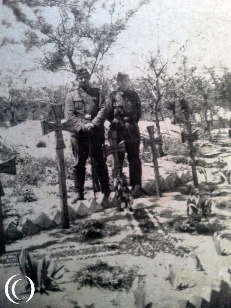 posing near a grave site, Unknown if they lost company members at this location in Italy