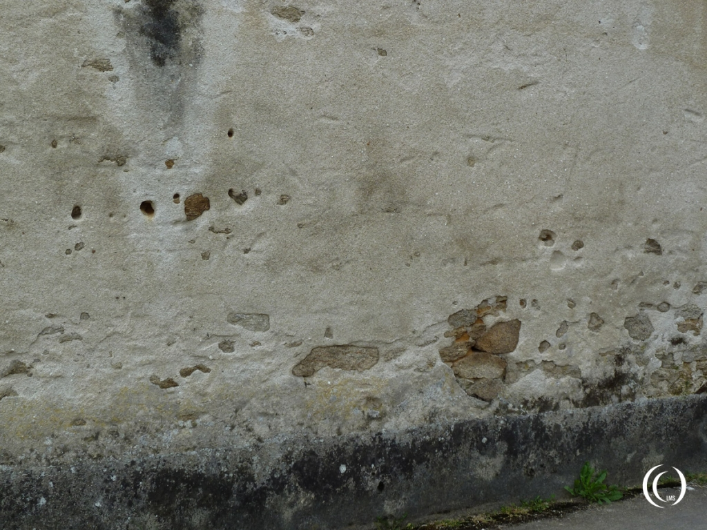 Wall next to Denis Wine and Spirits store marked with bullet holes