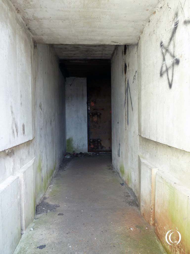 The corridor leading from the entrance door. Behind the steel door at the end is a small rifle port for defense purposes - Stelling Den Oever, Afsluitdijk, the Netherlands