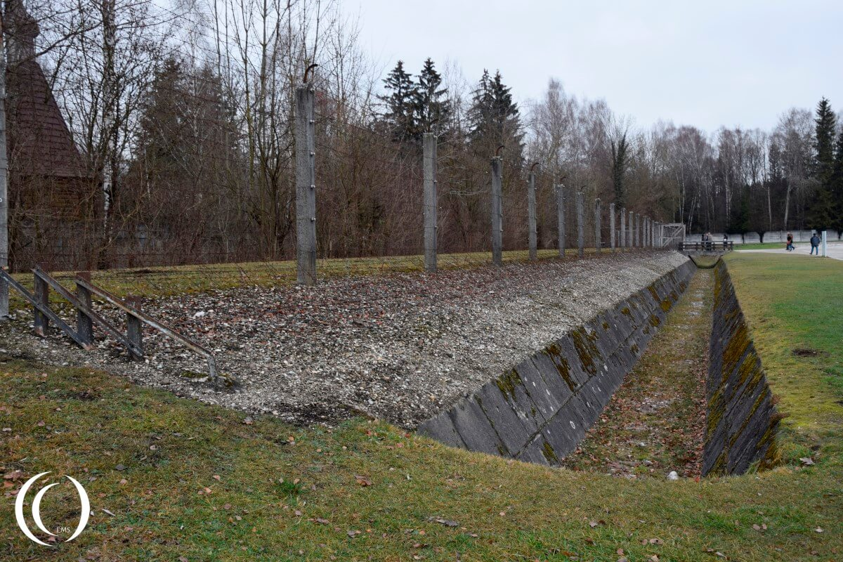 Moat and electrical fence on the inside of the fence in Dachau